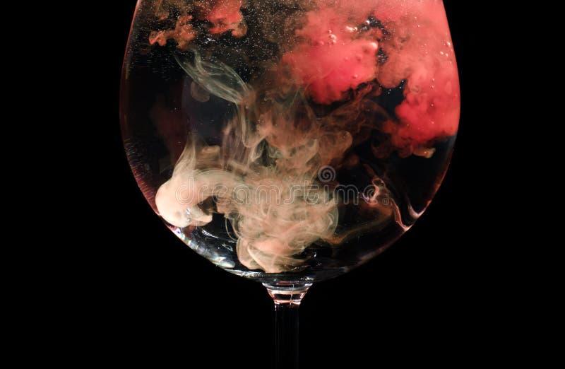 Κόκκινα σύννεφα σε ένα γυαλί κρασιού στοκ εικόνες