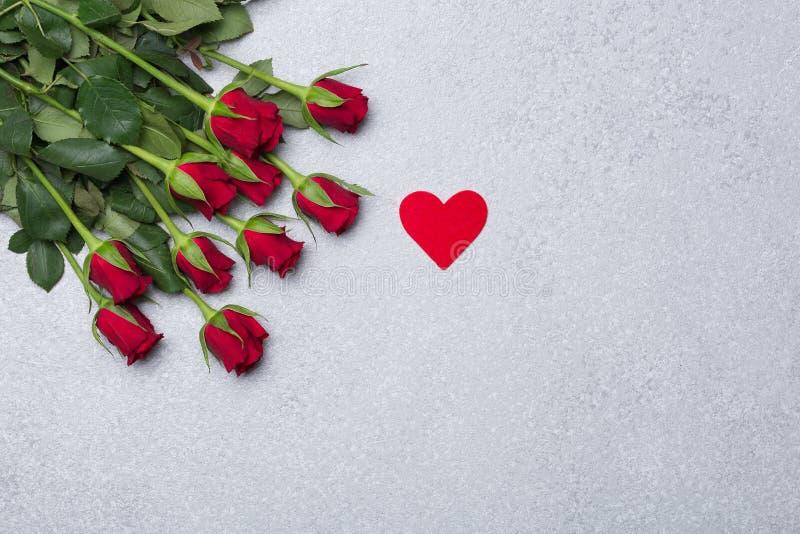 Κόκκινα τριαντάφυλλα και κόκκινη καρδιά στο γκρίζο υπόβαθρο στοκ φωτογραφία με δικαίωμα ελεύθερης χρήσης