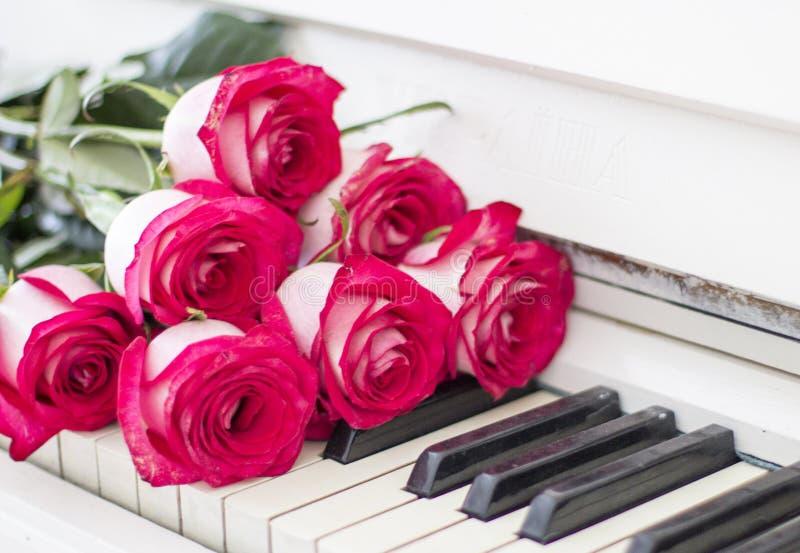 Κόκκινα τριαντάφυλλα πολυτέλειας σε ένα πιάνο Ανθοδέσμη των κόκκινων τριαντάφυλλων και του πιάνου στοκ φωτογραφία