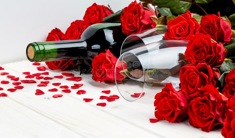 Κόκκινα τριαντάφυλλα και κρασί στο άσπρο υπόβαθρο στοκ εικόνες