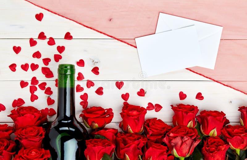 Κόκκινα τριαντάφυλλα και κρασί στο άσπρο υπόβαθρο στοκ φωτογραφίες με δικαίωμα ελεύθερης χρήσης