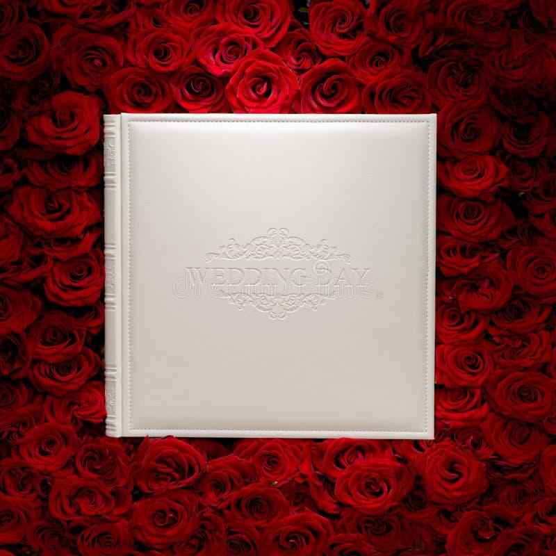 Κόκκινα τριαντάφυλλα με το άσπρο βιβλίο στοκ φωτογραφία με δικαίωμα ελεύθερης χρήσης