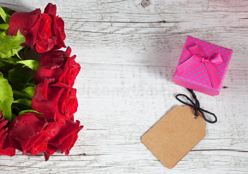 Κόκκινα τριαντάφυλλα με το μικρό ρόδινο κιβώτιο δώρων στοκ φωτογραφία με δικαίωμα ελεύθερης χρήσης
