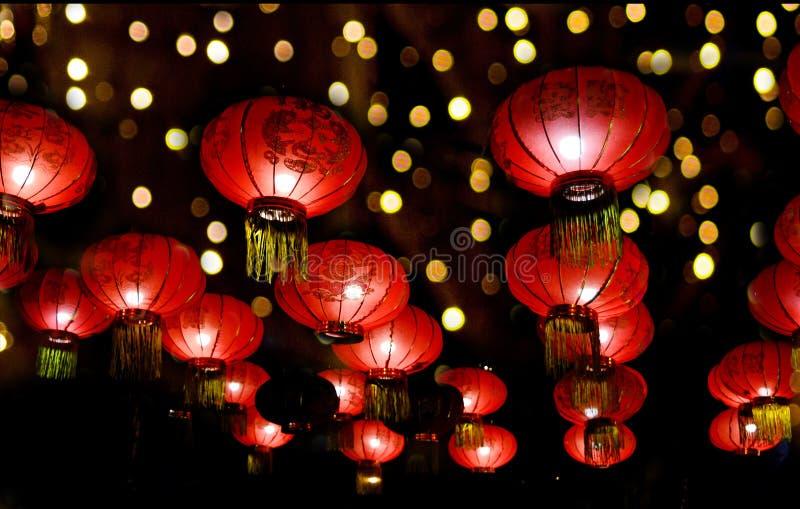 Κόκκινα φανάρια για την Κινέζικη Πρωτοχρονιά τη νύχτα, στο φόντο της πολύχρωμης μποκέ Διακόσμηση με φώτα τη νύχτα για στοκ εικόνα