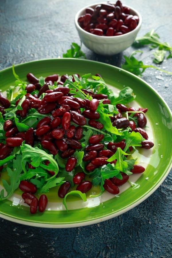 Κόκκινα φασόλια και άγρια υγιής σαλάτα πυραύλων σε ένα πράσινο πιάτο στοκ φωτογραφία