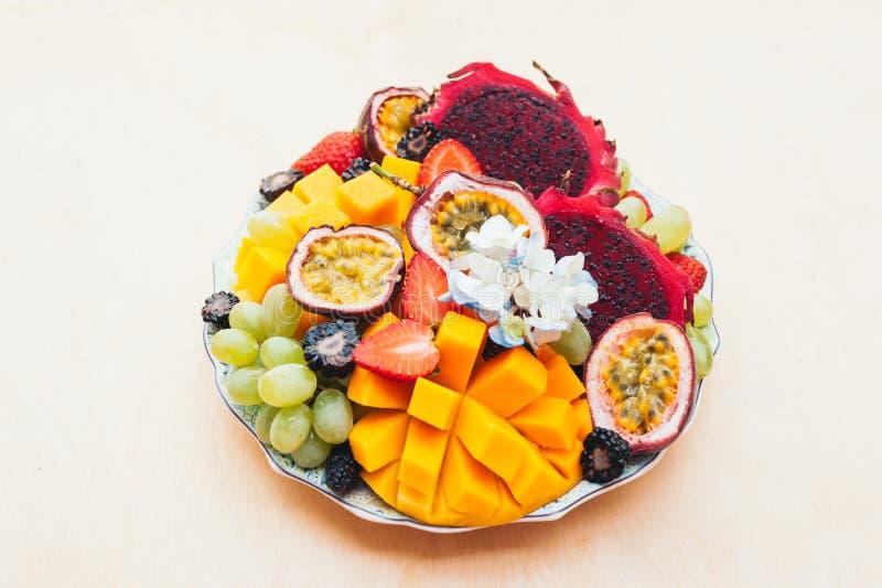Κόκκινα φρούτα, σταφύλια, μάγκο και φράουλα δράκων pitaya στο πιάτο στο άσπρο κλίμα Καλή διατροφή, φρούτα πλούσια σε βιταμίνες στοκ εικόνες