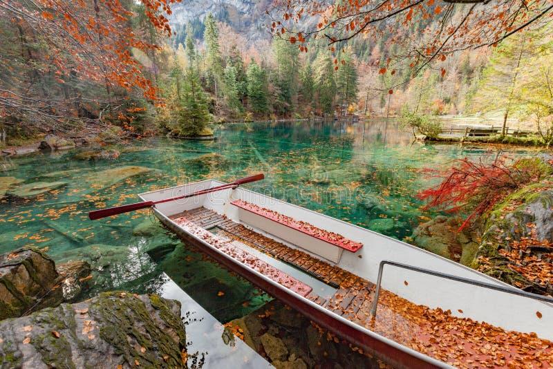 Κόκκινα φύλλα και κόκκινη βάρκα στο μπλε πάρκο φύσης λιμνών Blausee/, Kande στοκ εικόνα