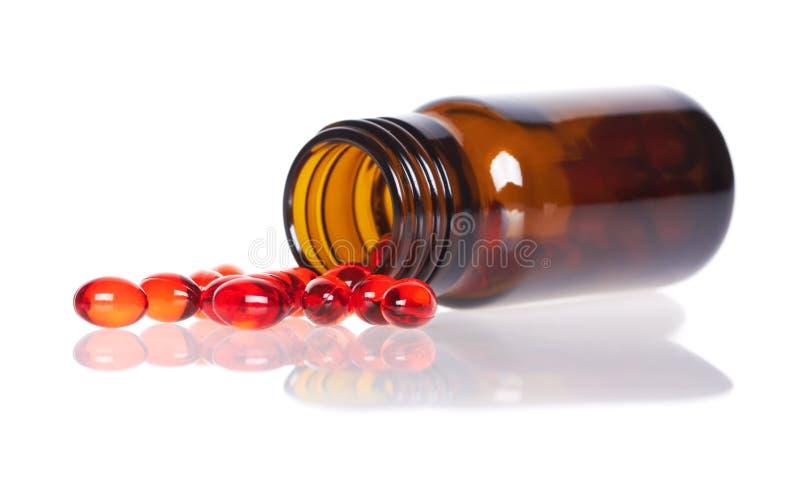 Κόκκινα χάπια ένα μπουκάλι χαπιών στοκ φωτογραφία με δικαίωμα ελεύθερης χρήσης