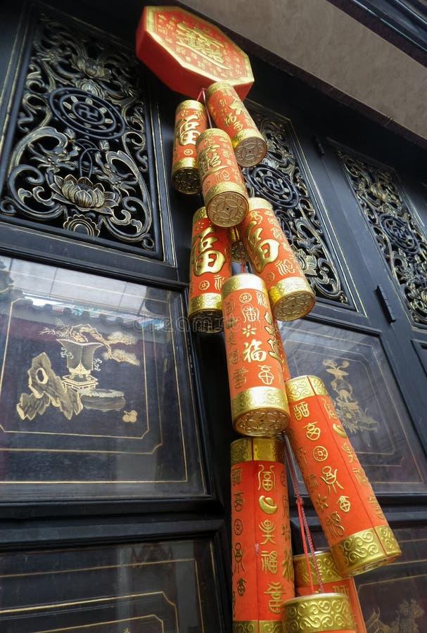 Κόκκινα χαρωπά κινεζικά νέα Firecrackers έτους που κρεμούν ως διακοσμήσεις στην ξύλινη πόρτα των λαρνάκων στοκ φωτογραφία με δικαίωμα ελεύθερης χρήσης