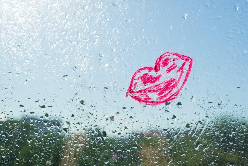 Κόκκινα χείλια φιλιών που χρωματίζονται με το κραγιόν στο παράθυρο με τις πτώσεις νερού Ο μπλε ηλιόλουστος ουρανός υποβάθρου, πτώ στοκ εικόνες με δικαίωμα ελεύθερης χρήσης