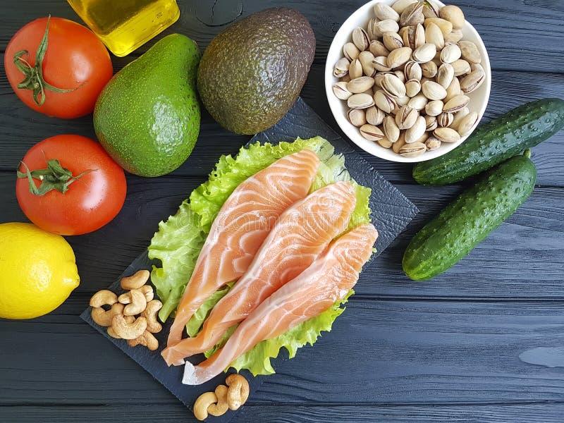 Κόκκινα ψάρια, οργανική επιλογή αβοκάντο συστατικών φρέσκια στην ξύλινη κουζίνα των δυτικών ανακαρδίων στοκ φωτογραφίες
