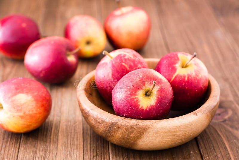 Κόκκινα ώριμα μήλα σε ένα ξύλινο πιάτο στοκ εικόνα με δικαίωμα ελεύθερης χρήσης