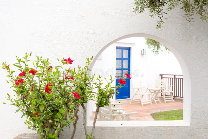 Κόκκινα hibiscus και παραδοσιακό ελληνικό σπίτι με την μπλε πόρτα στοκ εικόνες