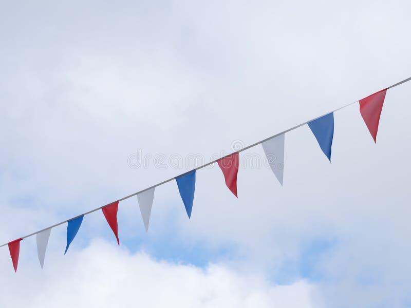 Κόκκινες, άσπρες και μπλε εορταστικές σημαίες υφάσματος στο κλίμα ουρανού Μορφές τριγώνων στοκ φωτογραφίες