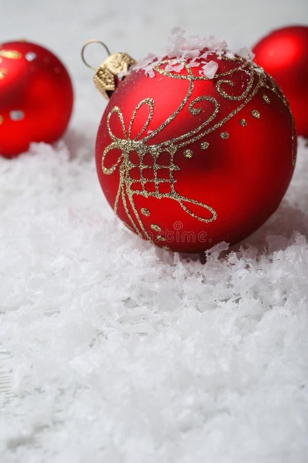 Κόκκινες διακοσμήσεις Χριστουγέννων στο τεχνητό χιόνι στοκ εικόνα