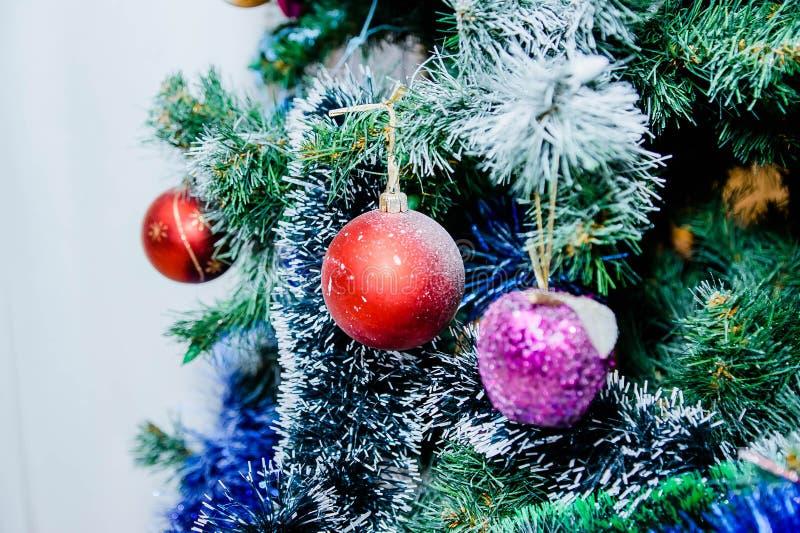 Κόκκινες και πορφυρές σφαίρες και άσπρη και μπλε γιρλάντα σε ένα χριστουγεννιάτικο δέντρο στοκ φωτογραφίες με δικαίωμα ελεύθερης χρήσης