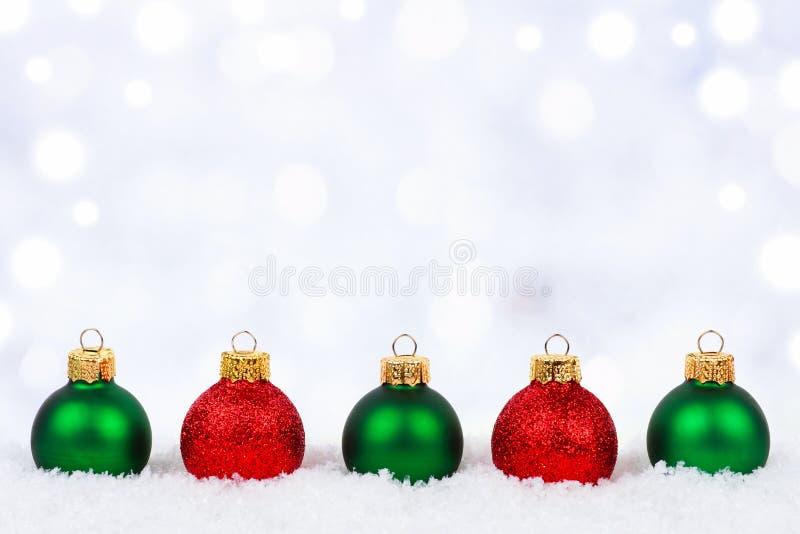 Κόκκινες και πράσινες διακοσμήσεις Χριστουγέννων στο χιόνι με το αστράφτοντας υπόβαθρο στοκ εικόνα