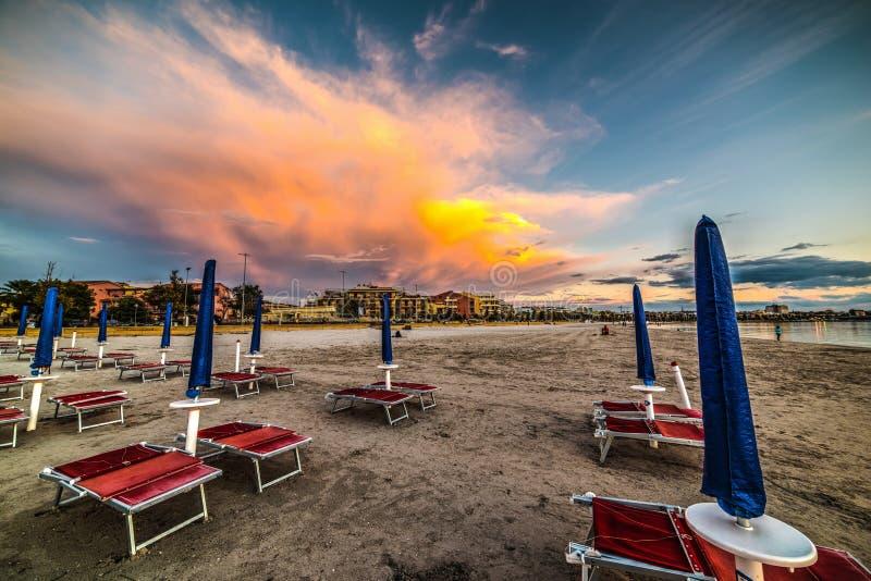 Κόκκινες καρέκλες και μπλε parasol στο σούρουπο στοκ εικόνα με δικαίωμα ελεύθερης χρήσης
