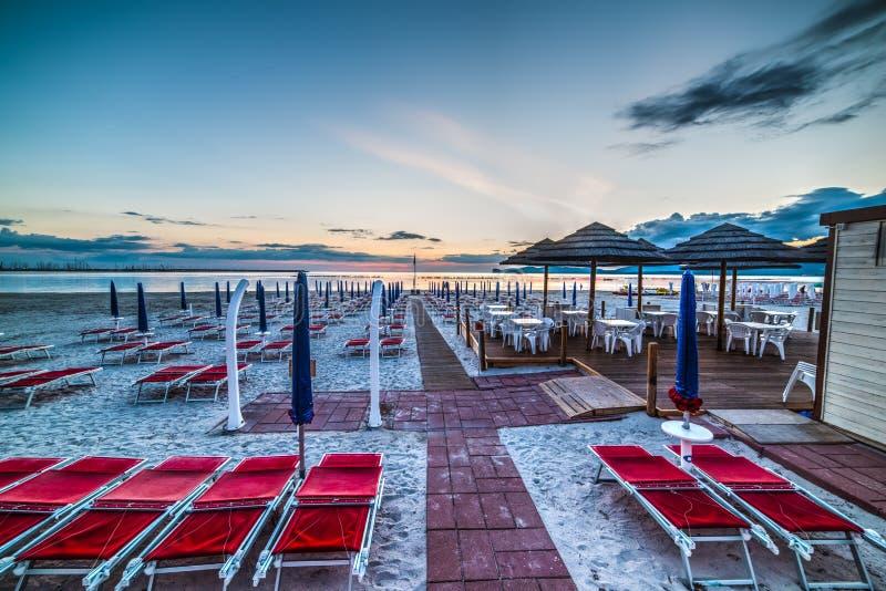 Κόκκινες καρέκλες και μπλε parasols στοκ φωτογραφία με δικαίωμα ελεύθερης χρήσης