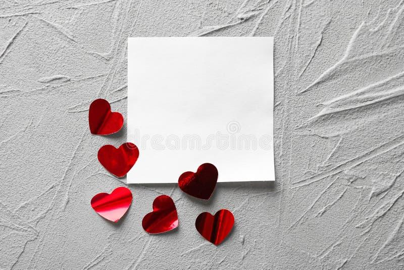 Κόκκινες καρδιές και κενή κάρτα στο γκρίζο κατασκευασμένο υπόβαθρο στοκ εικόνα