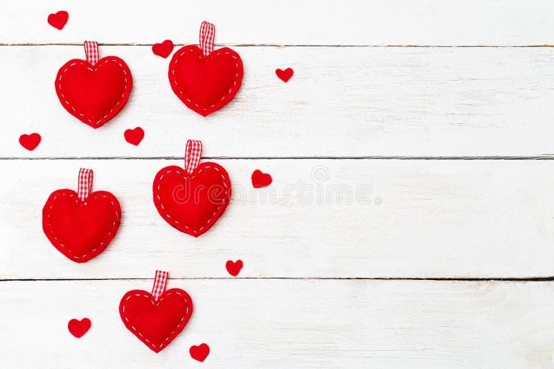 Κόκκινες καρδιές που ράβονται από αισθητός σε ένα άσπρο ξύλινο υπόβαθρο Αντίγραφο SPA στοκ εικόνες