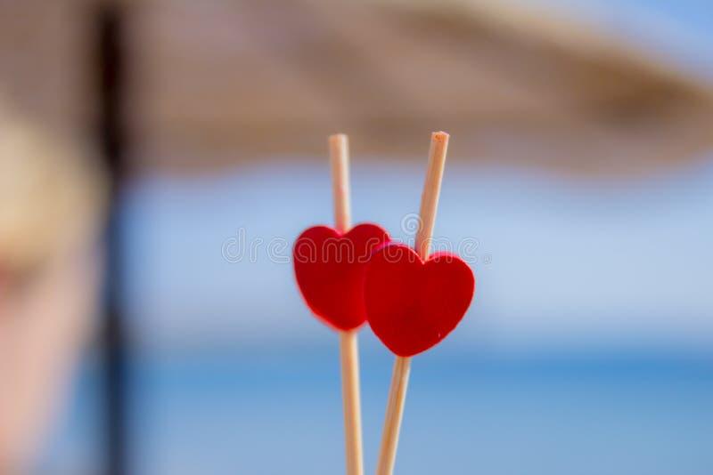 Κόκκινες καρδιές ως δώρο για την ημέρα του βαλεντίνου Η καρδιά είναι αγάπη πτώσης Υπόβαθρο ημέρας βαλεντίνων ομπρελών παραλιών θά στοκ φωτογραφίες