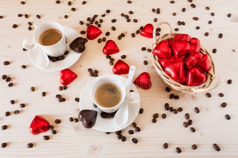 Κόκκινες καρδιές σοκολάτας σε μικρό καλάθι και δύο φλιτζάνια του καφέ στοκ εικόνα