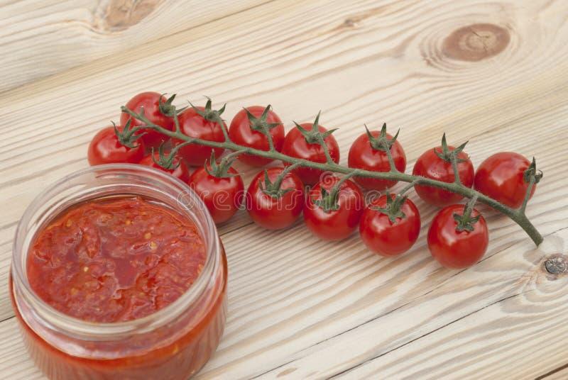 Κόκκινες ντομάτες σε έναν κλάδο και έναν τοματοπολτό στοκ φωτογραφία