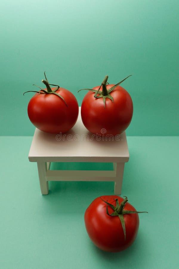 Κόκκινες ντομάτες σε μια άσπρη καρέκλα στοκ εικόνα με δικαίωμα ελεύθερης χρήσης