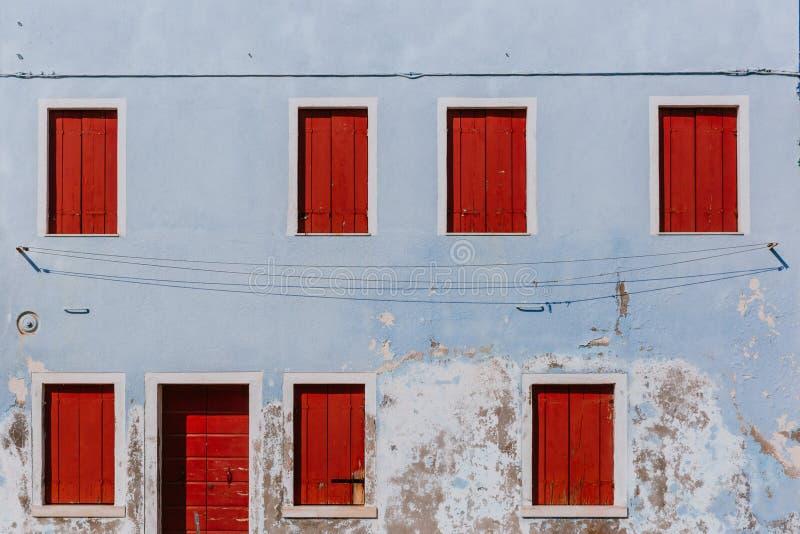 Κόκκινες ξύλινες παράθυρα και πόρτα στον παλαιό ανοικτό μπλε τοίχο, στο islan στοκ εικόνες