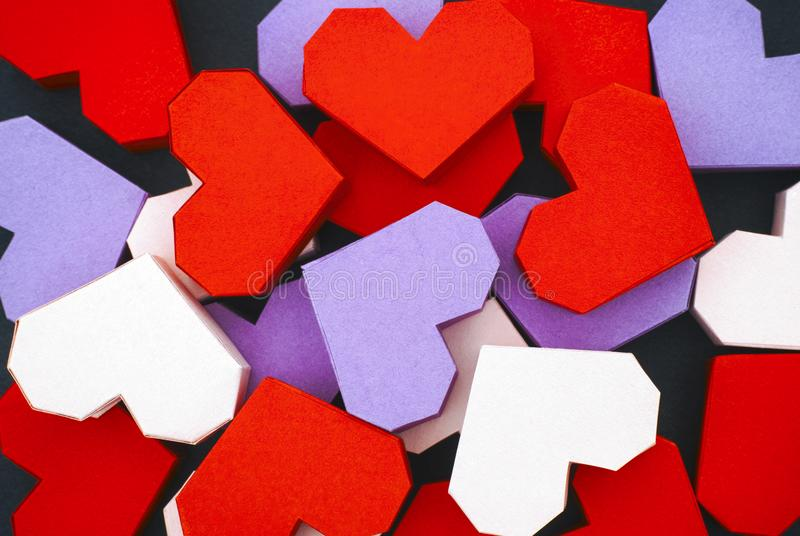 Κόκκινες, πορφυρές και ανοικτό ροζ καρδιές origami στο μαύρο υπόβαθρο στοκ εικόνες με δικαίωμα ελεύθερης χρήσης