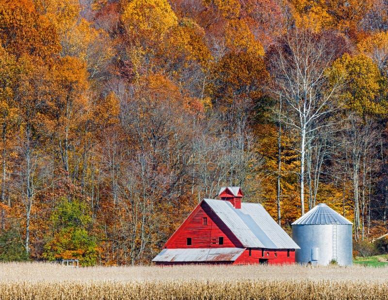 Κόκκινες σιταποθήκη και βουνοπλαγιά φθινοπώρου στοκ φωτογραφίες