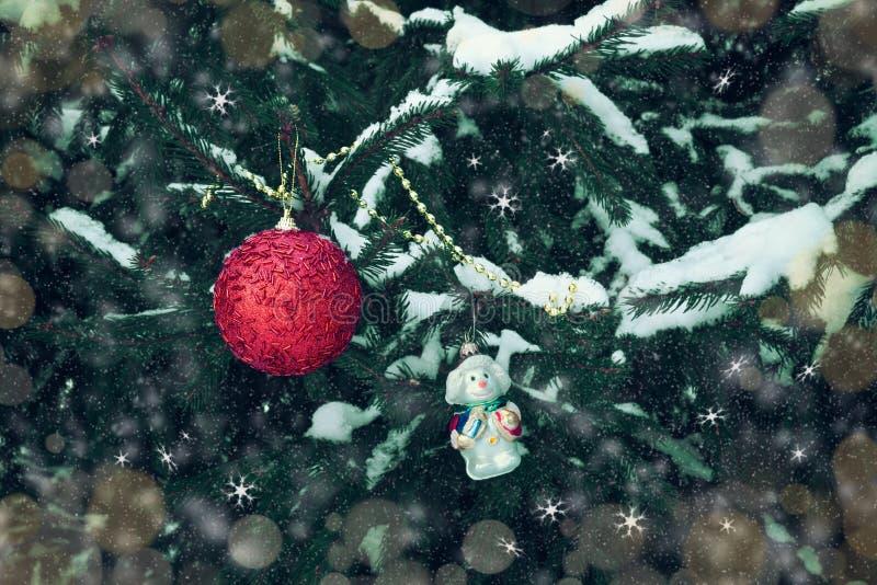 Κόκκινες σφαίρα Χριστουγέννων και διακόσμηση Χριστουγέννων χιονανθρώπων στον κλάδο δέντρων στοκ εικόνες