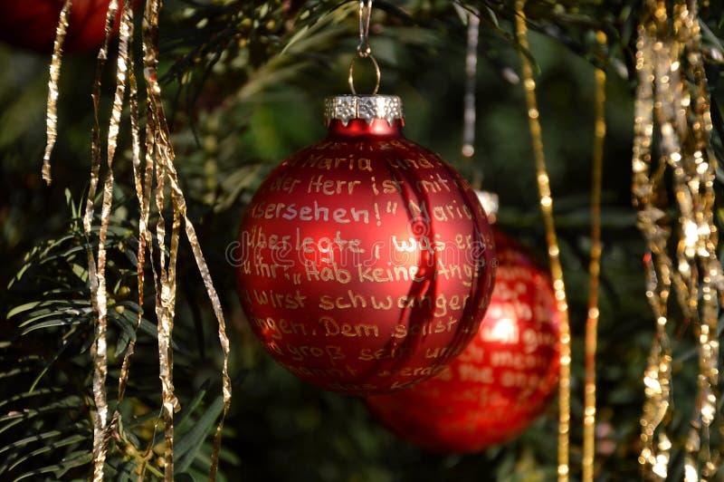 Κόκκινες σφαίρες Χριστουγέννων με τη χρυσή εγγραφή στοκ εικόνες