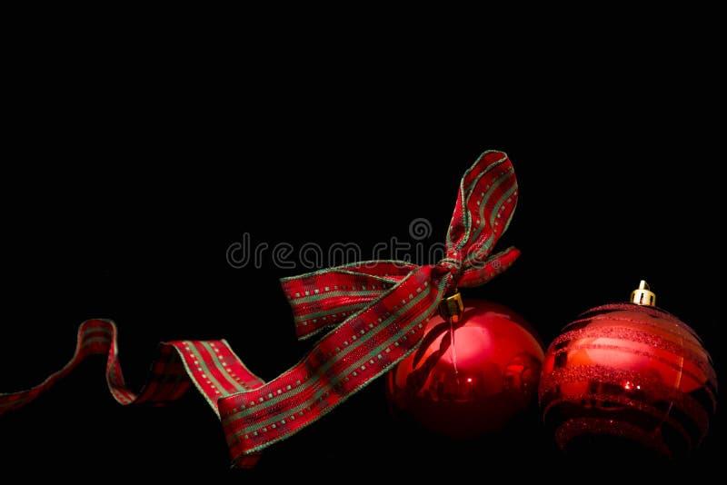 Κόκκινες σφαίρες Χριστουγέννων που απομονώνονται σε ένα μαύρο υπόβαθρο στοκ εικόνες