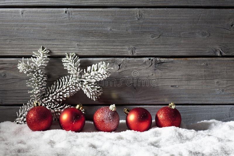 Κόκκινες σφαίρες Χριστουγέννων στο σωρό του χιονιού ενάντια στον ξύλινο τοίχο στοκ φωτογραφία