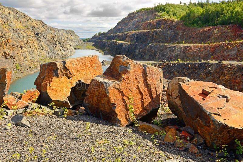Κόκκινες τεράστιες πέτρες σε ένα εγκαταλειμμένο ορυχείο στοκ εικόνες