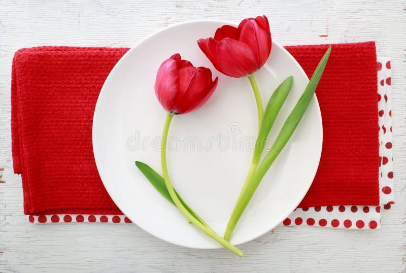 Κόκκινες τουλίπες στο άσπρο πιάτο στοκ φωτογραφία με δικαίωμα ελεύθερης χρήσης