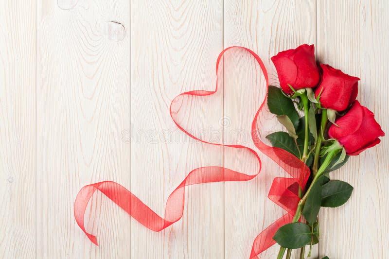 Κόκκινες τριαντάφυλλα και κορδέλλα μορφής καρδιών πέρα από το ξύλο στοκ εικόνα