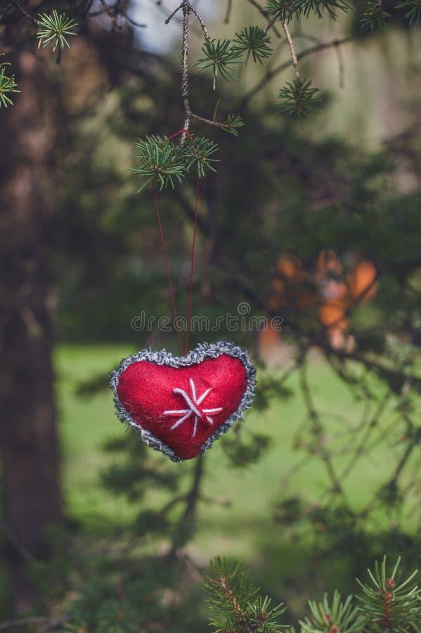Κόκκινη ένωση διακοσμήσεων Χριστουγέννων καρδιών στο δέντρο στοκ εικόνα με δικαίωμα ελεύθερης χρήσης