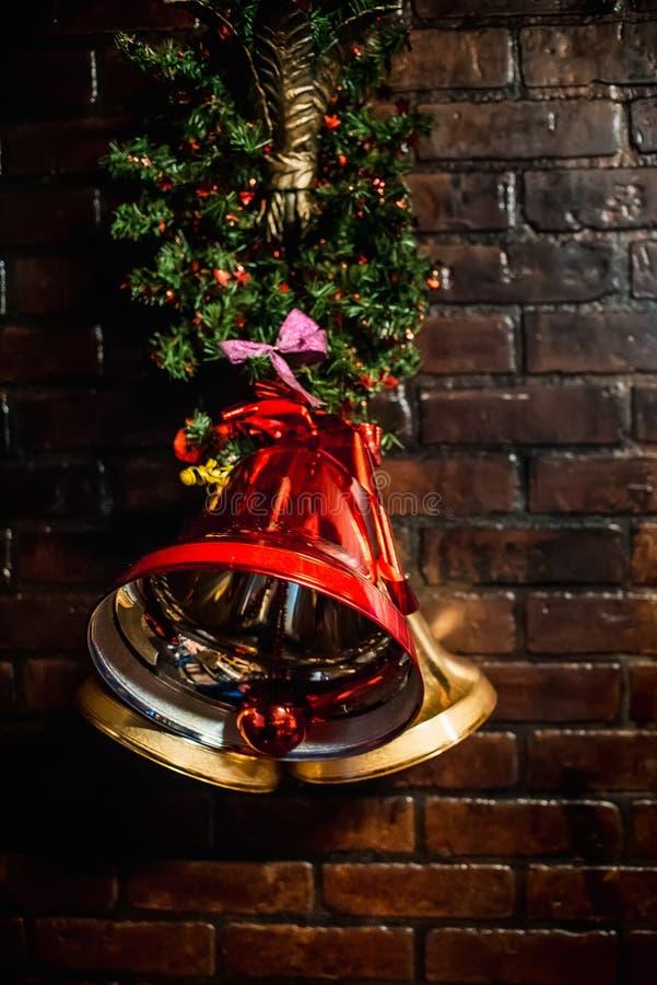 Κόκκινη ένωση κουδουνιών Χριστουγέννων στο τουβλότοιχο ως διακοσμητική διακόσμηση Χριστουγέννων στοκ εικόνες