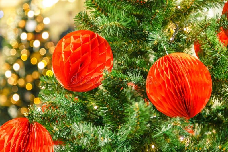 Κόκκινη ένωση μπιχλιμπιδιών κάτω από έναν κλάδο ενός χριστουγεννιάτικου δέντρου πεδίο βάθους ρηχό στοκ φωτογραφίες