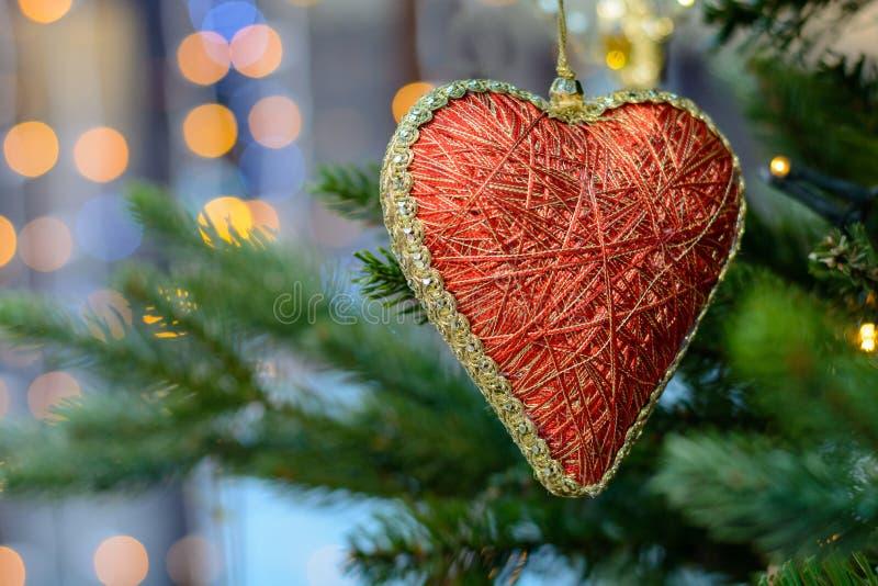 Κόκκινη ένωση παιχνιδιών καρδιών στο χριστουγεννιάτικο δέντρο στοκ φωτογραφία