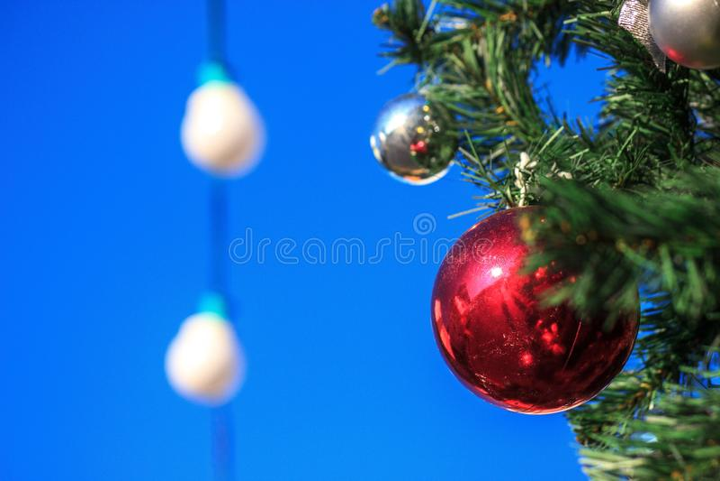 Κόκκινη ένωση σφαιρών στο χριστουγεννιάτικο δέντρο ως διακόσμηση στο υπόβαθρο του μπλε ουρανού και των φαναριών στοκ φωτογραφίες με δικαίωμα ελεύθερης χρήσης