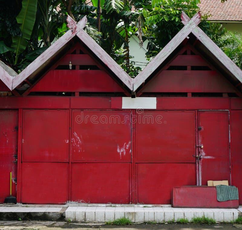 Κόκκινη αποθήκη με τον πράσινο κήπο μέσα στη φωτογραφία που λαμβάνεται στο Σεμαράνγκ Ινδονησία στοκ εικόνες