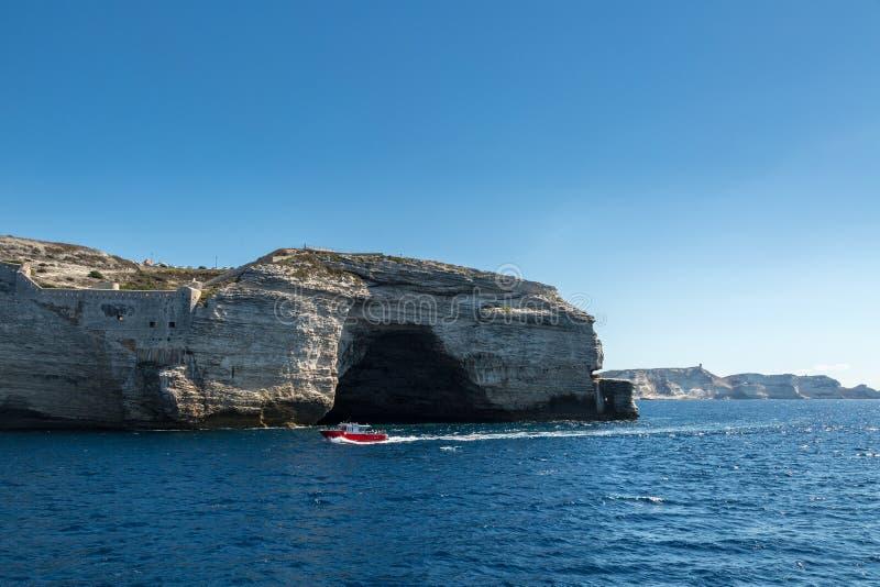 Κόκκινη βάρκα γύρου που περνά τη σπηλιά στους άσπρους απότομους βράχους σε Bonifacio στοκ φωτογραφία
