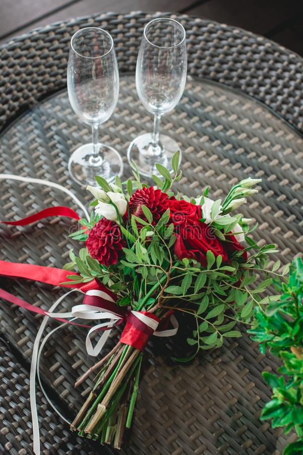 Κόκκινη γαμήλια ανθοδέσμη σε έναν πίνακα γυαλιού κενά γυαλιά δύο σαμπάνιας στοκ φωτογραφία