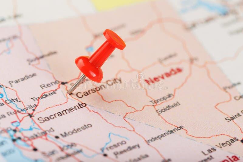 Κόκκινη γραφείου βελόνα σε έναν χάρτη των ΗΠΑ, της Νεβάδας και της κύριας πόλης του Carson Χάρτης Νεβάδα κινηματογραφήσεων σε πρώ στοκ εικόνα