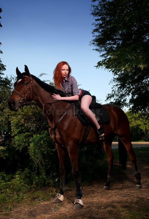 κόκκινη γυναίκα συνεδρίασης αλόγων τριχώματος στοκ εικόνα με δικαίωμα ελεύθερης χρήσης