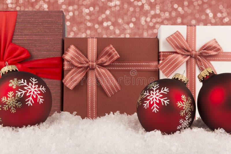 Κόκκινη διακόσμηση σφαιρών Χριστουγέννων στο χιόνι Φω'τα Bokeh και κιβώτια δώρων στο υπόβαθρο στοκ εικόνα με δικαίωμα ελεύθερης χρήσης